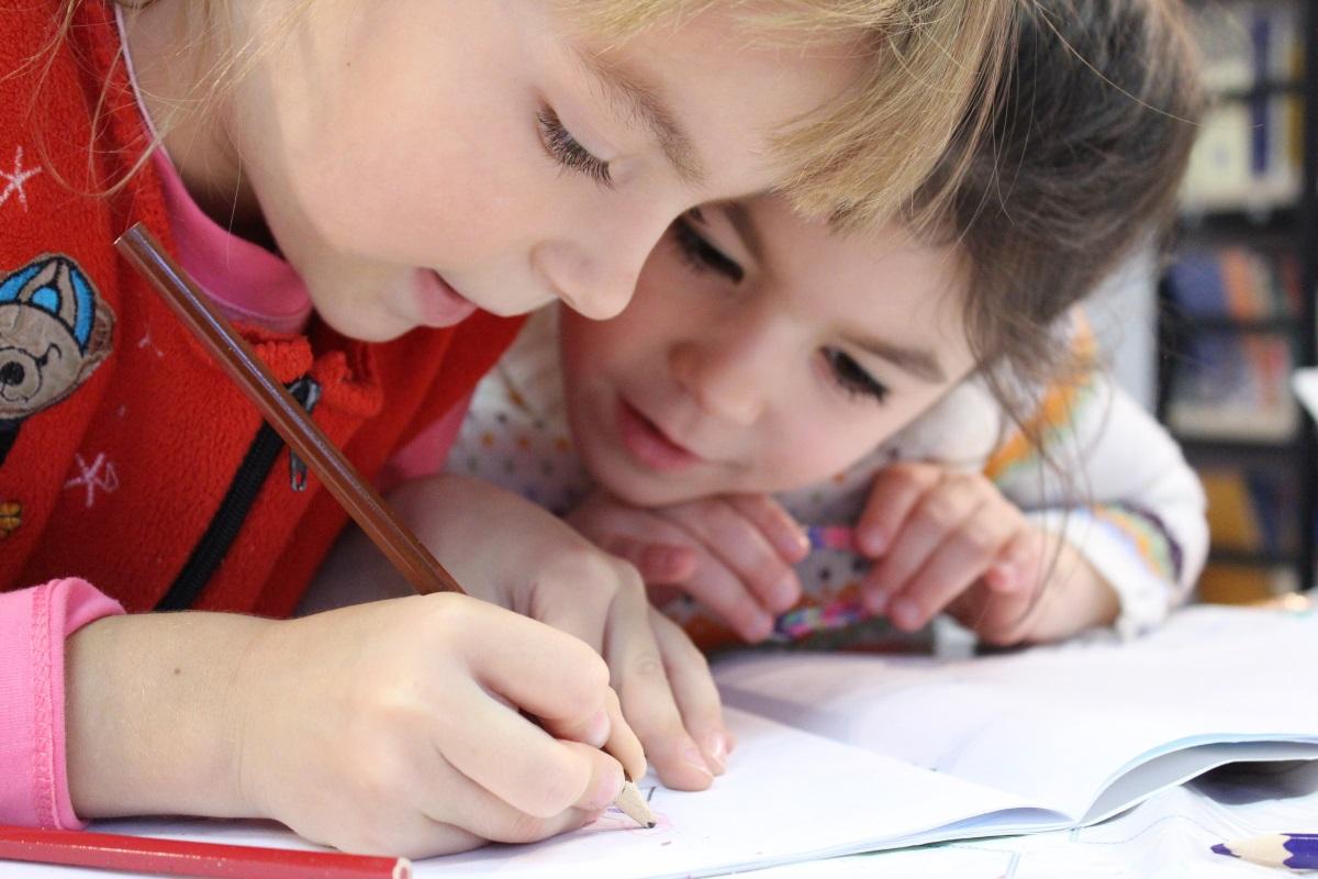 Zwei Kinder malen ein Bild mit Holzstiften