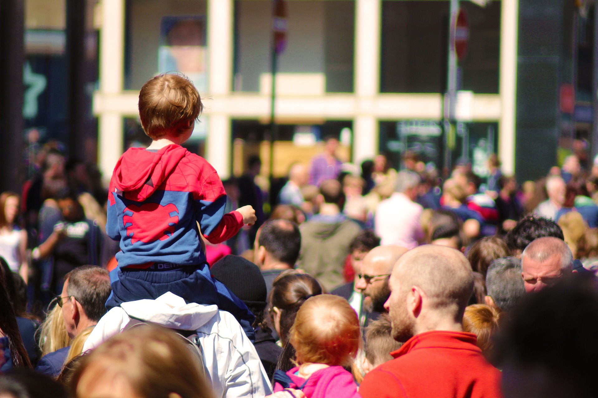 Eine Menschenmenge: Viele Menschen, junge und ältere, sind von hinten zu sehen.