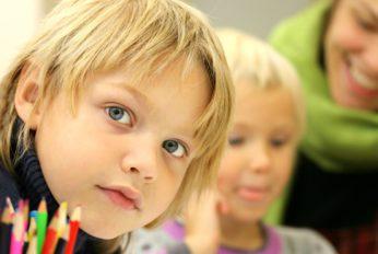 Junge in der Schule schaut in die Kamera, vor sich bunte Stifte
