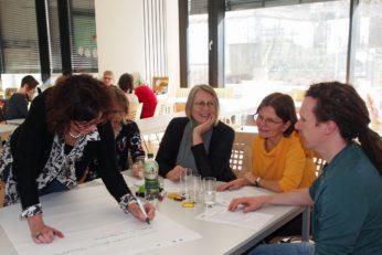 Das Bild zeigt die Auftaktveranstaltung der BHP Fachgruppen in Baden-Württemberg, Teilnehmende sitzen an einem Tisch und arbeiten gemeinsam